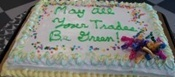 Graduation cake with May all Your Trades Be Green written in icing