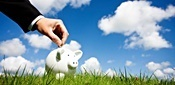 Hand putting money into a piggy bank sitting the grass on a beautiful day with clouds in the sky